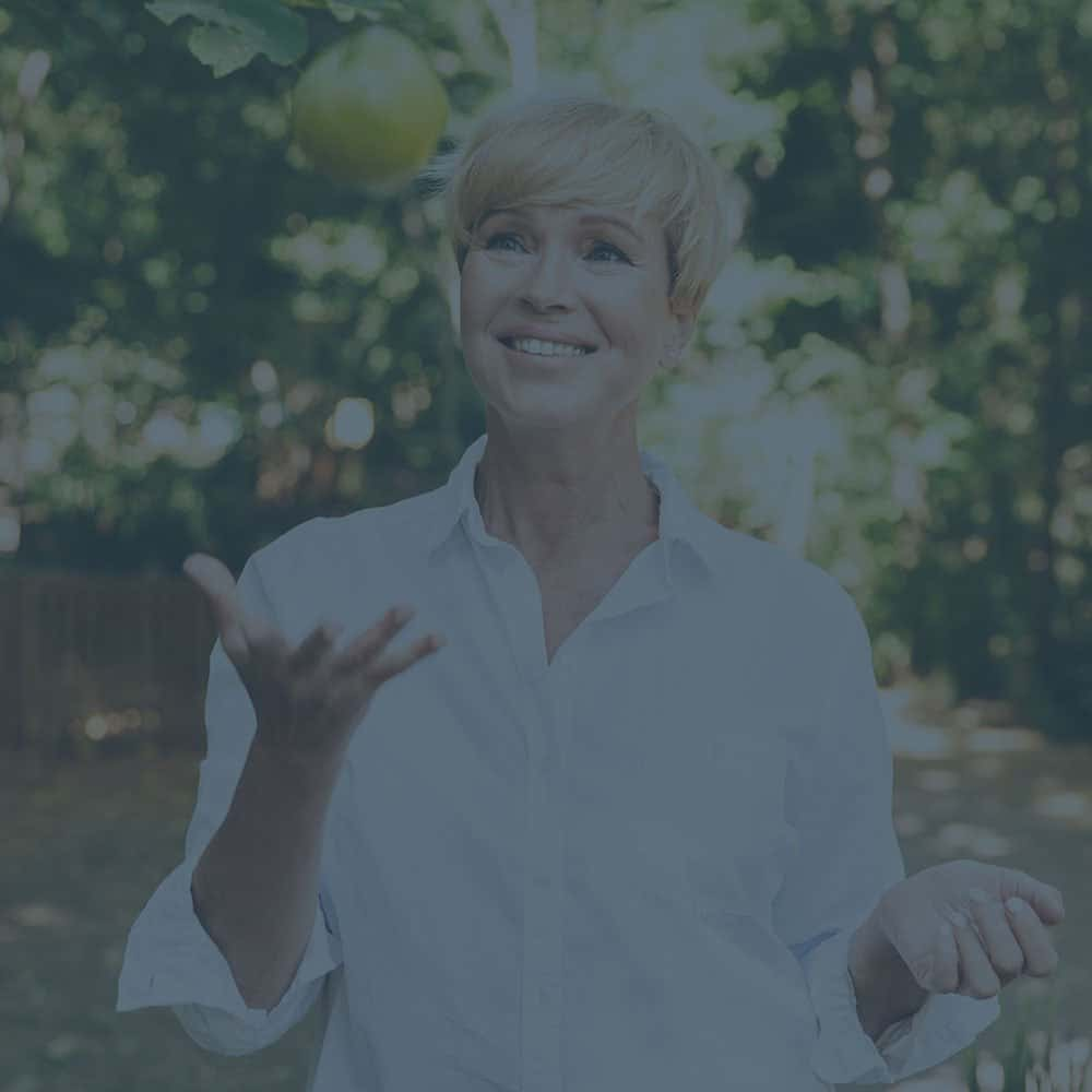 TMJ Treatment offers the independence to eat this crisp apple this older woman throws up in the air. Our dentist can give you the relief you need.