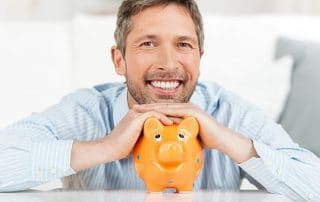 man with a piggy bank shows off his smile