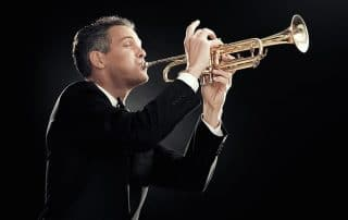 Handsome man in a tuxedo playing the trumpet