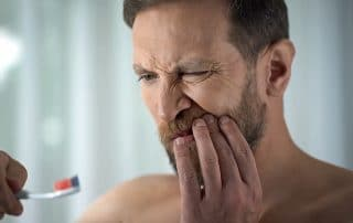 Man touching tooth in pain