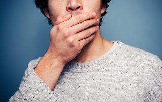 Man covering up his mouth as a warning sign