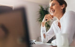 beautiful woman sitting at her computer, smiling