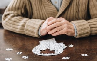 Man sitting quietly in front of a puzzle with missing pieces