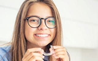 Teen girl with large eye glasses smiles and holds her Invisalign clear braces