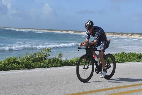 Dr Collins riding his bike next to a beautiful beach